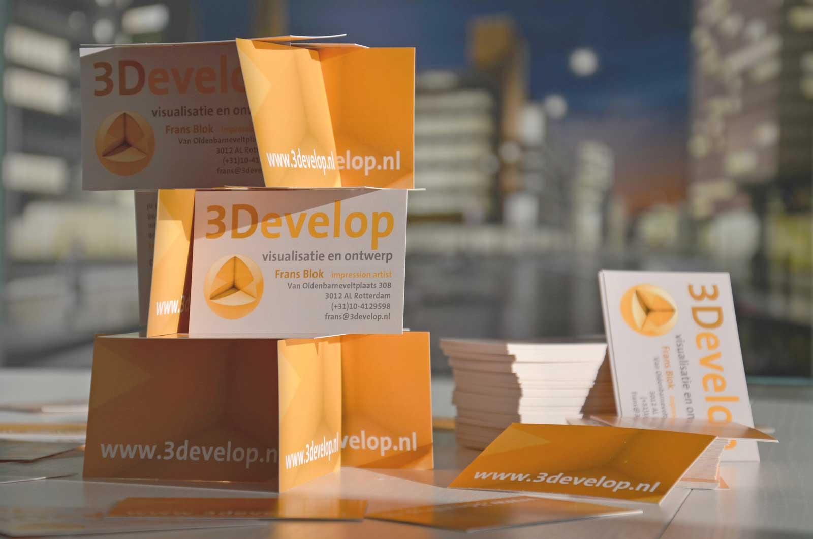 Kaartenhuis gebouwd van visitekaartjes van 3Develop met de door het bedrijf gemaakte visualisatie van Dudok's Bijenkorf vaag op de achtergrond