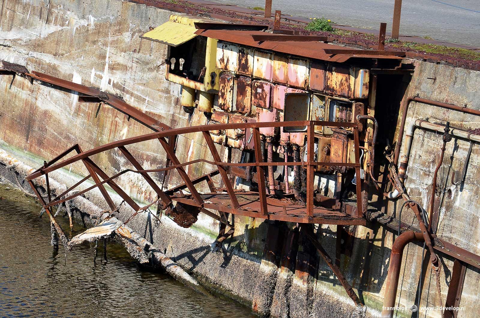 Roestige en gedeeltelijk ingestorte constructie tegen een ruwe betonnen kade in Vlissingen