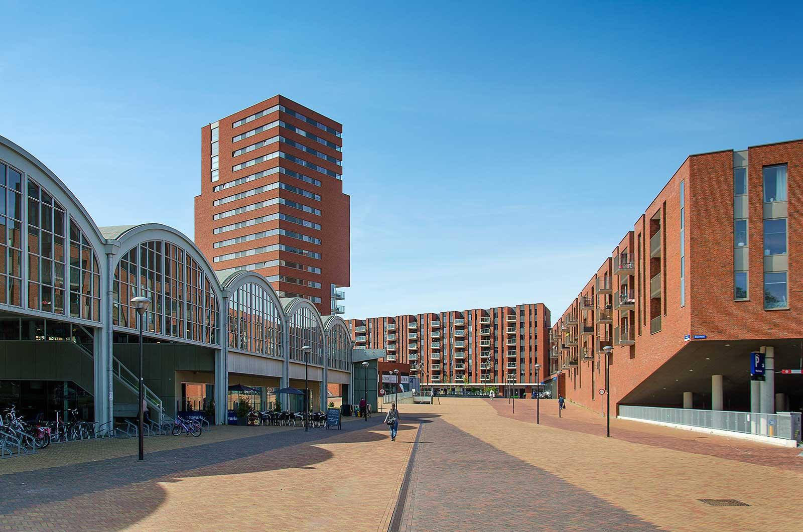 Entree tot winkelcentrum Meerrijk, Eindhoven, met de hergebruikte hangar en met nieuwe blokken opgetrokken in roodbruine baksteen