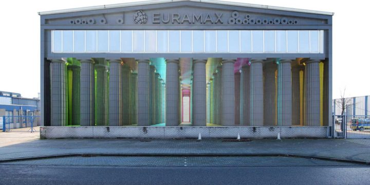 Image of an aluminium Greek temple, iluminated with lights in many colors, mounted on panels on the facade of the Euramax factory in Roermond, The Netherlands