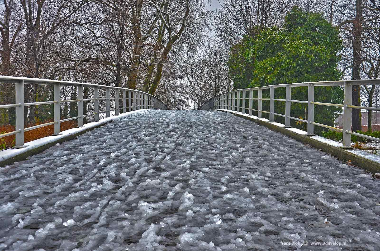 De brug in het Museumpark bij de Kunsthal in Rotterdam op een winterdag met half gesmolten en weer opgevroren sneeuw