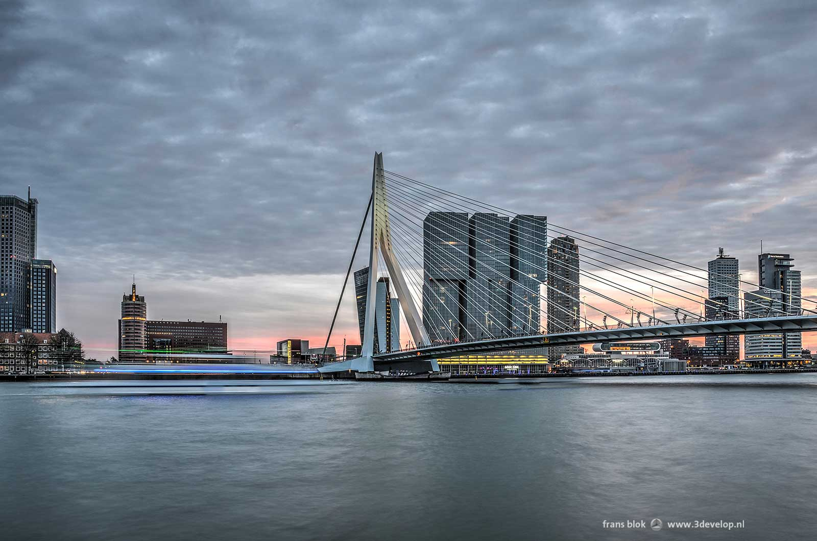 Evening image of the river Nieuwe Maas, Erasmus Bridge and Kop van Zuid neighbourhood in Rotterdam