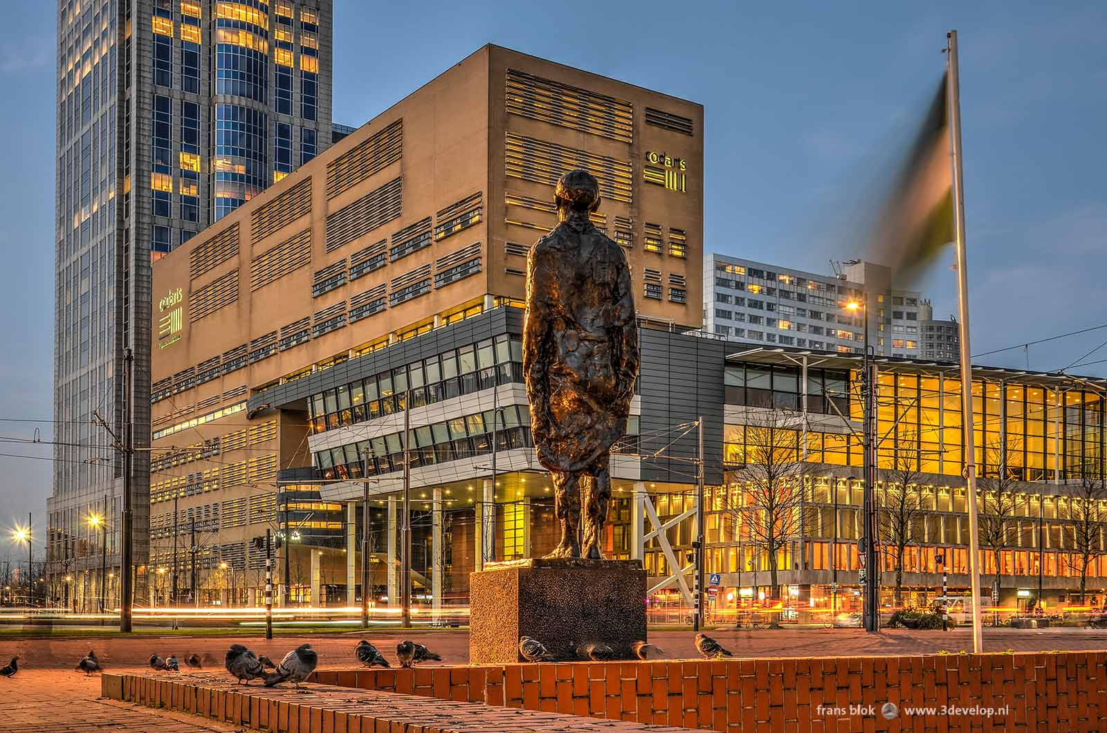 Evening image of Kruisplein in Rotterdam, with stripes from car lights and imperturbablepigeons around the resistance monument