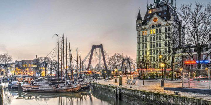 Zonsopkomst op een bijna wolkenloze dag in Rotterdam, met de Willemsbrug, het witte Huis en de Oude Haven