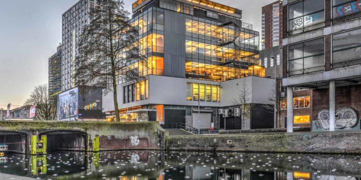 Wederopbouwmonument Huf, gefotografeerd vanaf het Grote Kerkplein, aan het eind van de middag in december, met het gebouw en de binnenverlichting reflecterend in de Delftsevaart