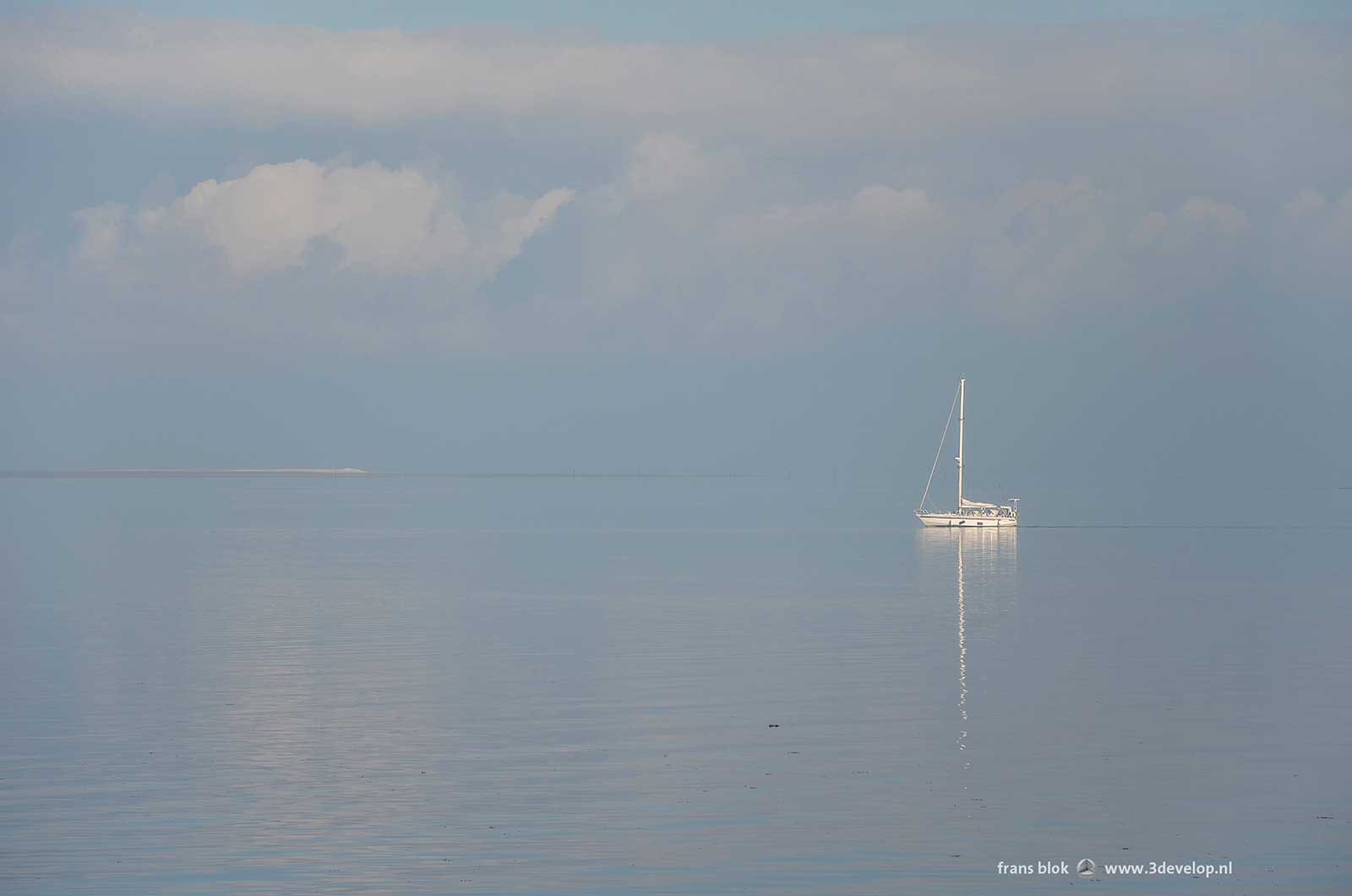 Sailing boat on an almost mirrorlike Eastern Scheldt with enormous clouds above the horizon.