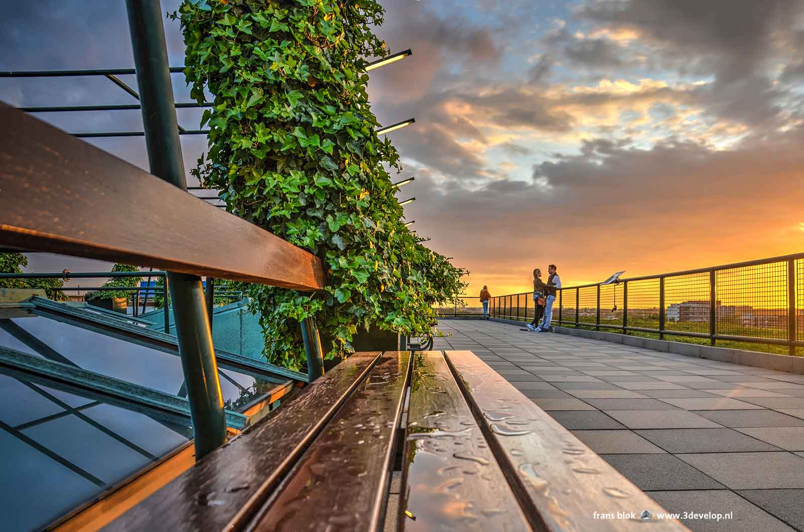 Bench on the roof of the Groothandelsgebouw during sunset, with a couple in a romantic mood in the background