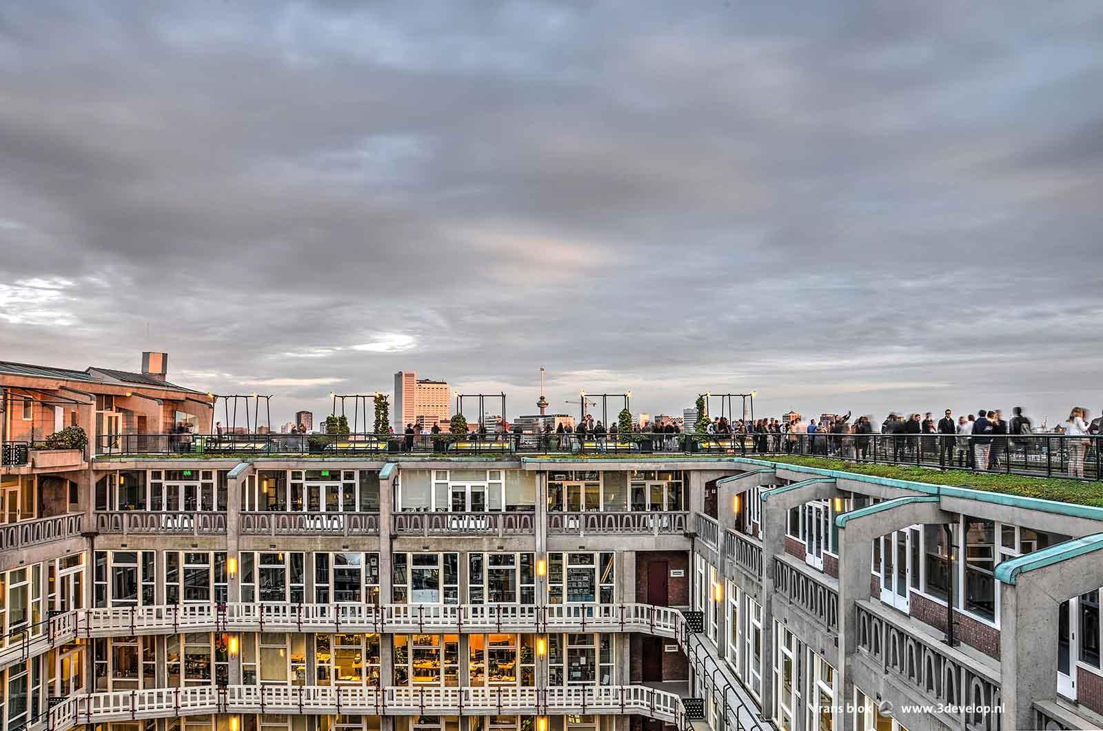 Bezoekers bewonderen de skyline van Rotterdam vanaf het dak van het Groothandelsgebouw, met op de voorgrond een van de binnenhoven van Maaskant's wederopbouw-monument