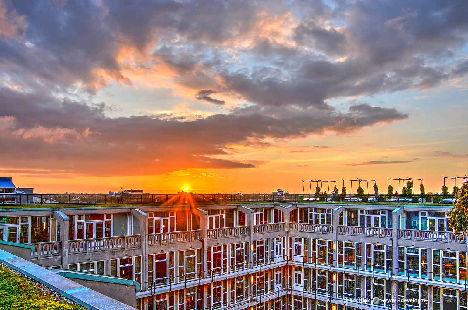 Zonsondergang gezien vanaf het dak van het Groothandelsgebouw in Rotterdam met een van de binnenhoven van dat gebouw op de voorgrond