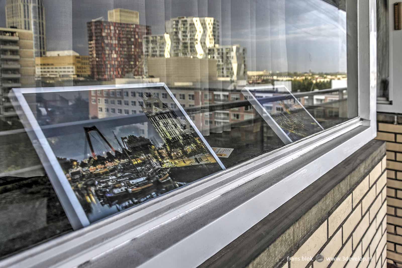 Foto van het Witte Huis en de Willemsbrug, ingelijst achter het raam in een van de Lijnbaanflats, waarin ook de reflectie van het Calypso-gebouw te zien is.