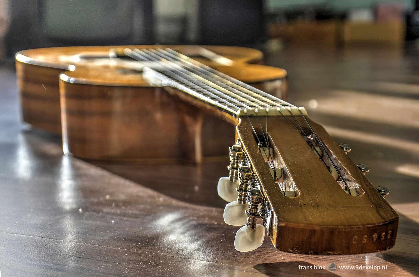 Foto van een akoestische gitaar met nieuwe stemmechanieken, liggen op een laminaatvloer.