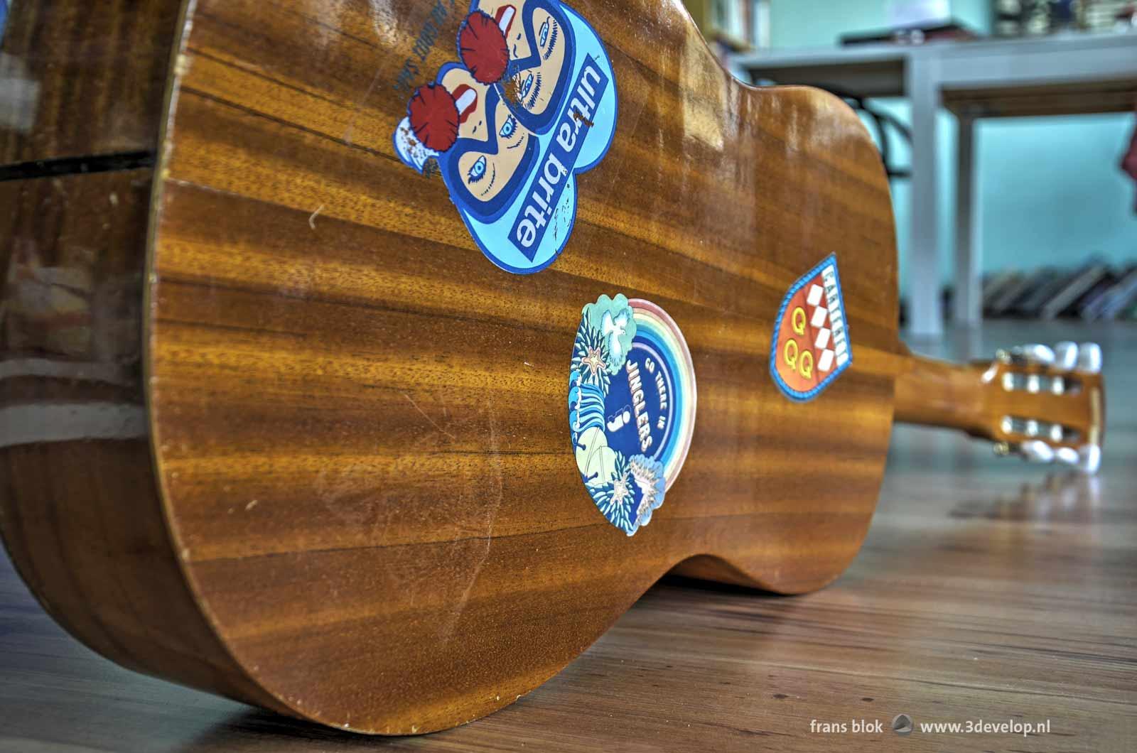 Stickers uit de jaren zestig op de rug van een akoestische gitaar