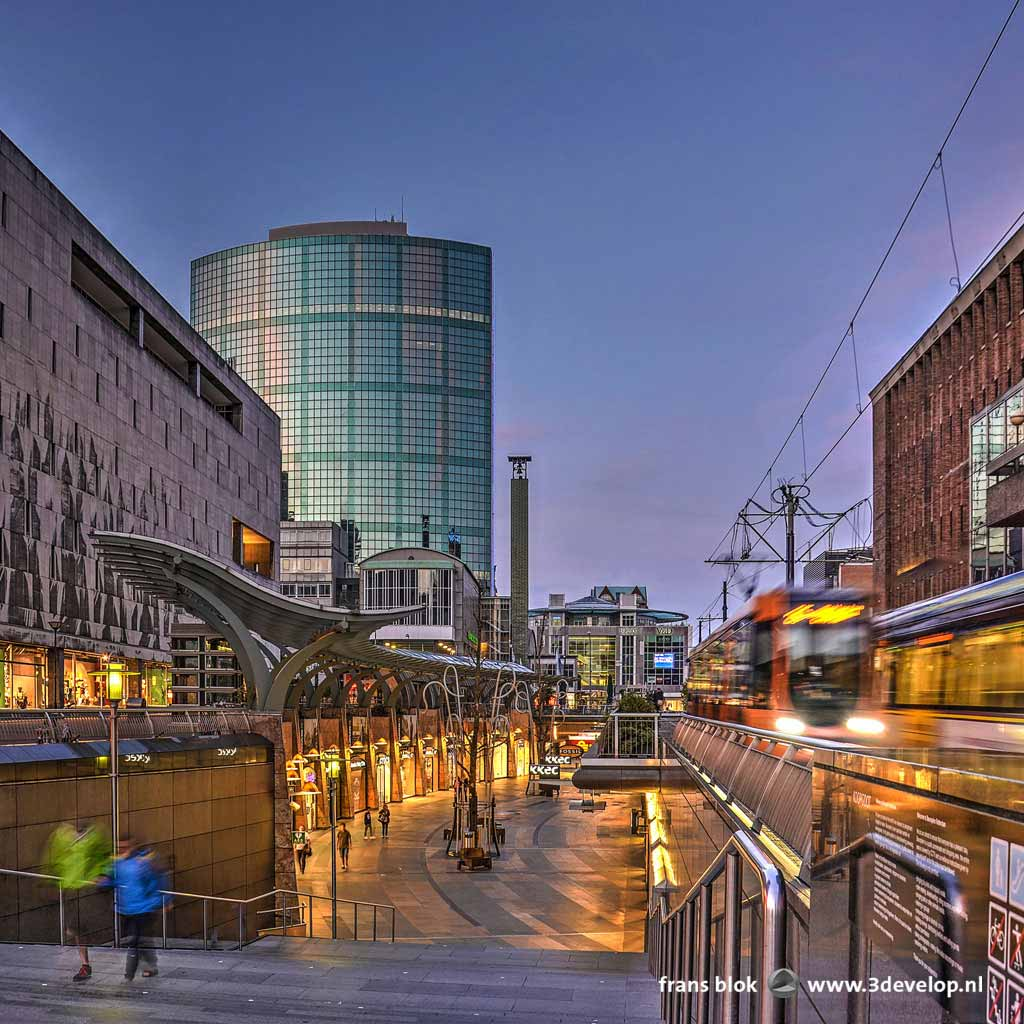 Photo made during the blue hour at the Koopgoot, or shopping gutter in Rotterdam, with illuminated shop windows as well as trams passing by.