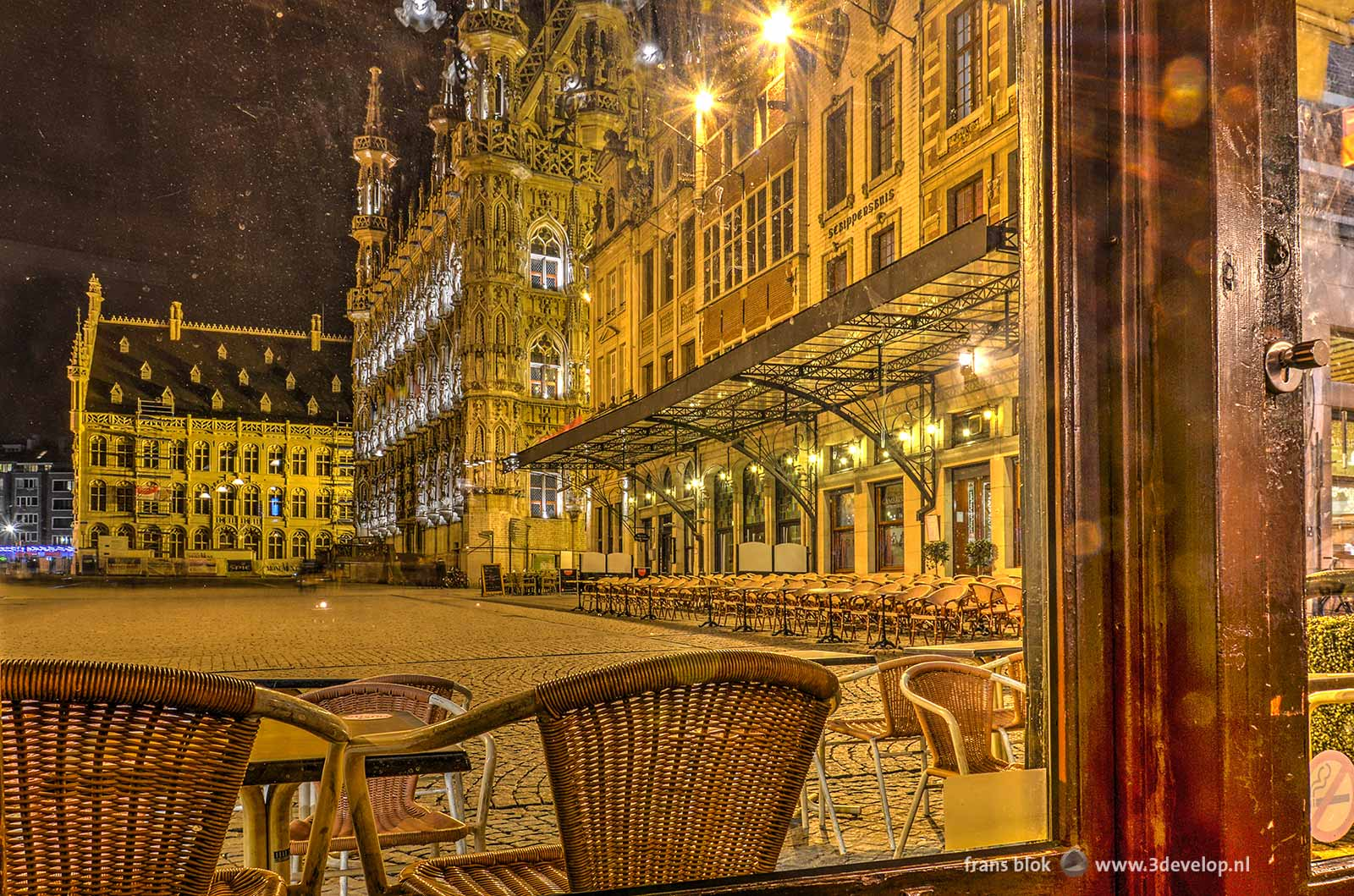 Photo of the City Hall and the Market Square in Leuven made at night through the window of a pub.