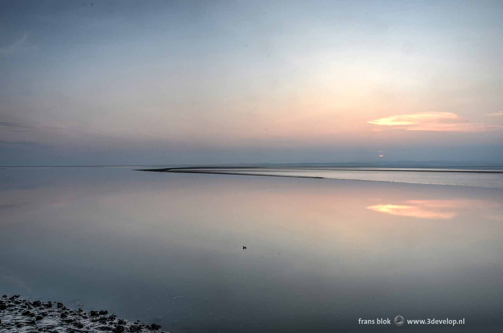 Sunset above the Bay of morecambe in Lancashire, England, with a black mudflat and an extremely smooth sea