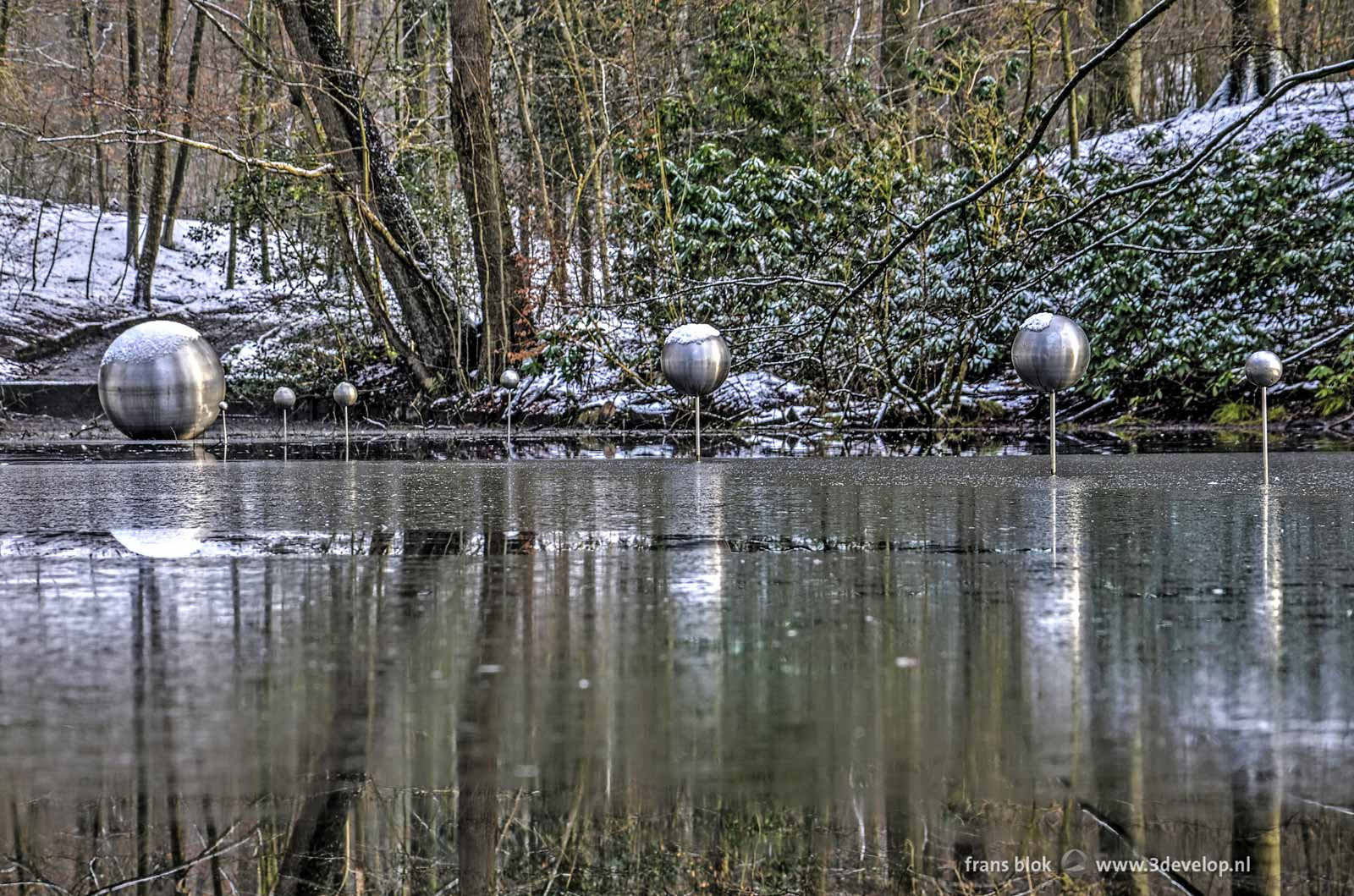 Photo in a wintery atmosphere of the sculpture Skies Captured by Henrietta Lehtonen, a forest planetarium in the Cold Pond in Sonsbeek Park in Arnhem, The Netherlands