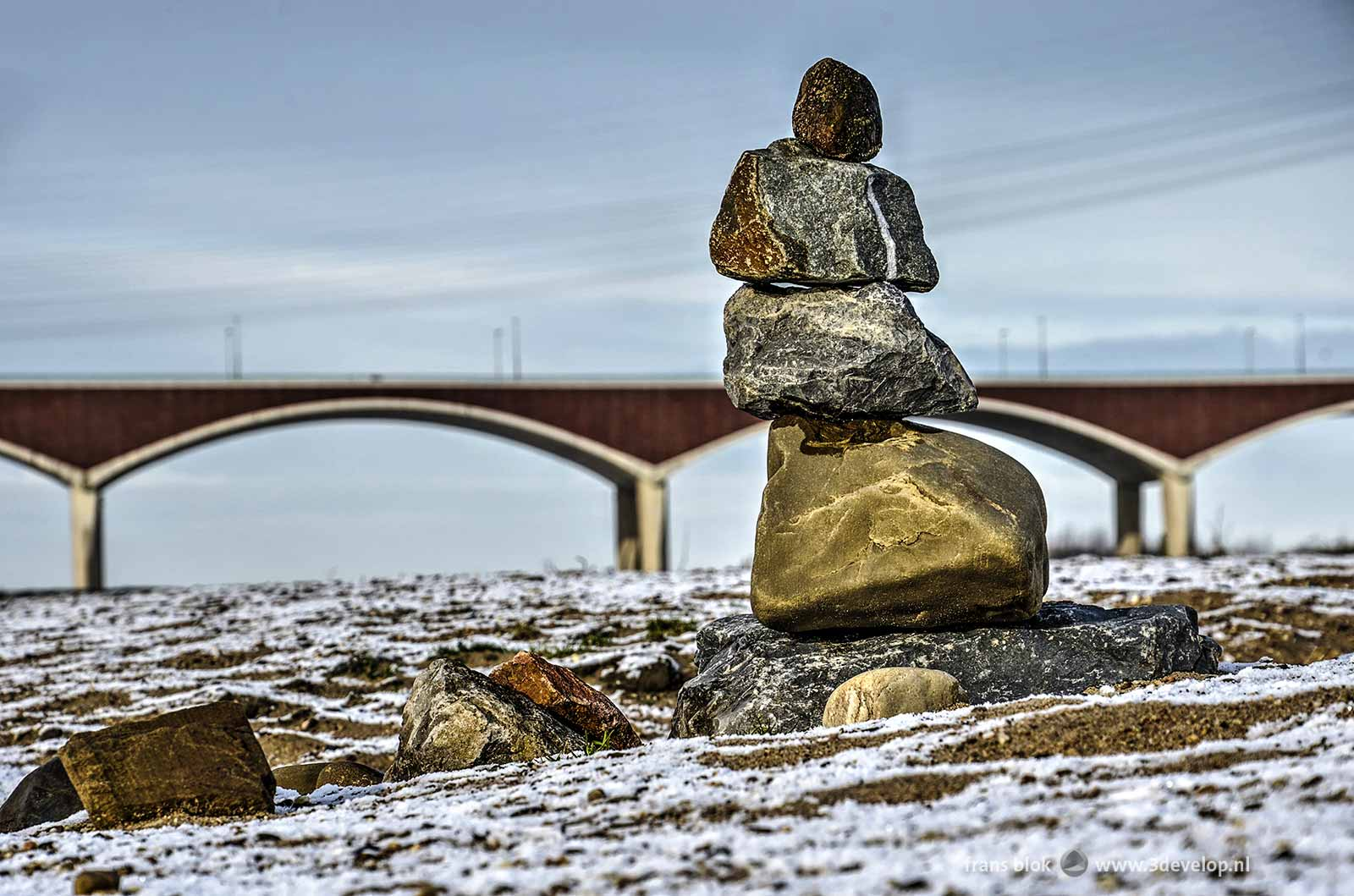 Photo of a cairn in the floodplains near Nijmegen, covered with a thin layer of snow, with city bridge The Crossing in the background
