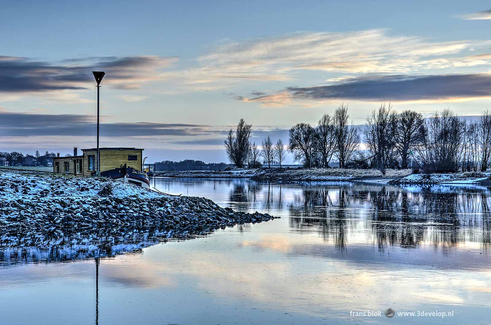 Photo of the IJssel river near Zutphen on a winter afternoon around sunset, with a yellow houseboat and snow on the riverbanks