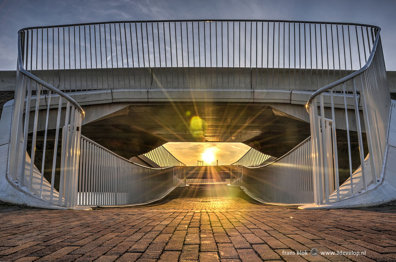 The setting sun shines exactly through one of the pedestrian shortcuts under the Lentloper bridge in Nijmegen