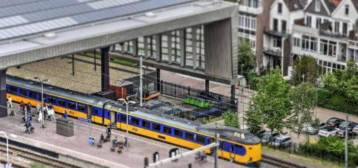 Het Madurodam- of Miniworld-effect op een foto van het het centraal station in Rotterdam met geelblauwe trein van de Nederlandse Spoorwegen