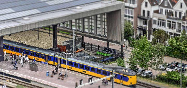 The Miniworld or Madurodam effect on a photo of Rotterdam Central Station featuring a yellow bleu Dutch Railways train