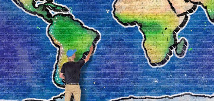 Met behulp van Photoshop in scene gezette actiefoto van de auteur werkend aan een graffiti-wereldkaart op een muur van tien bij vijf meter.