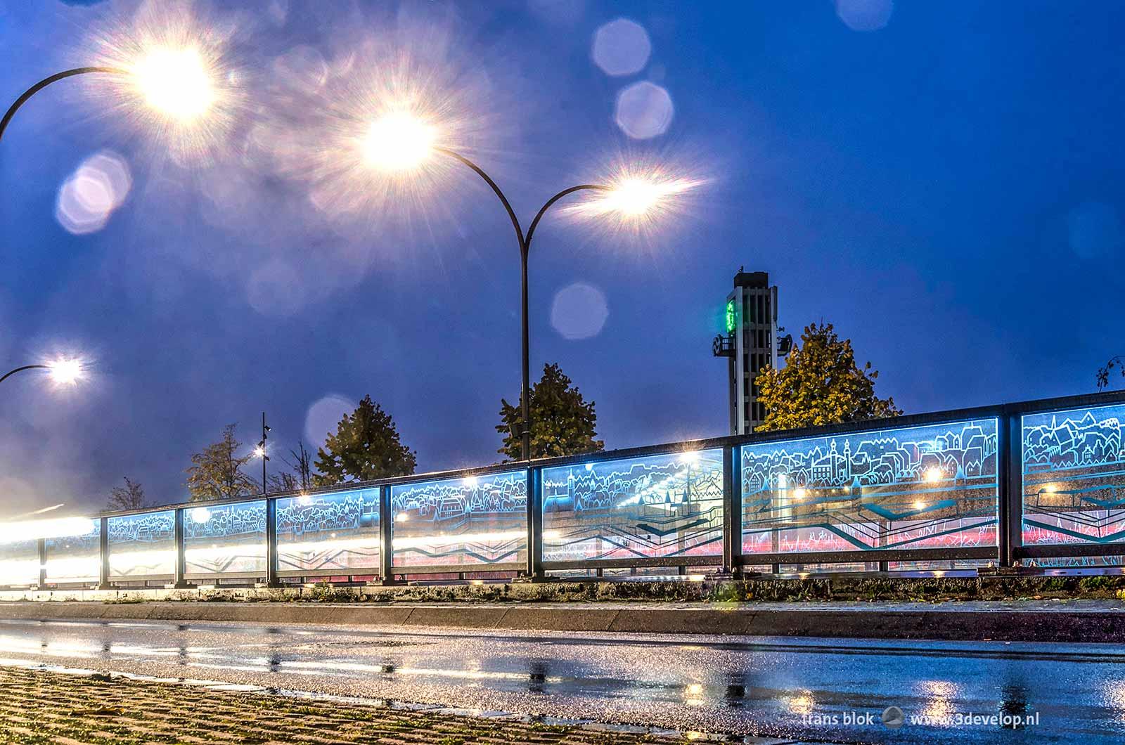 Foto van de glaspanelen op het Koninginneplein in Venlo, gemaakt met regenachtig weer tijdens het blauwe uur.