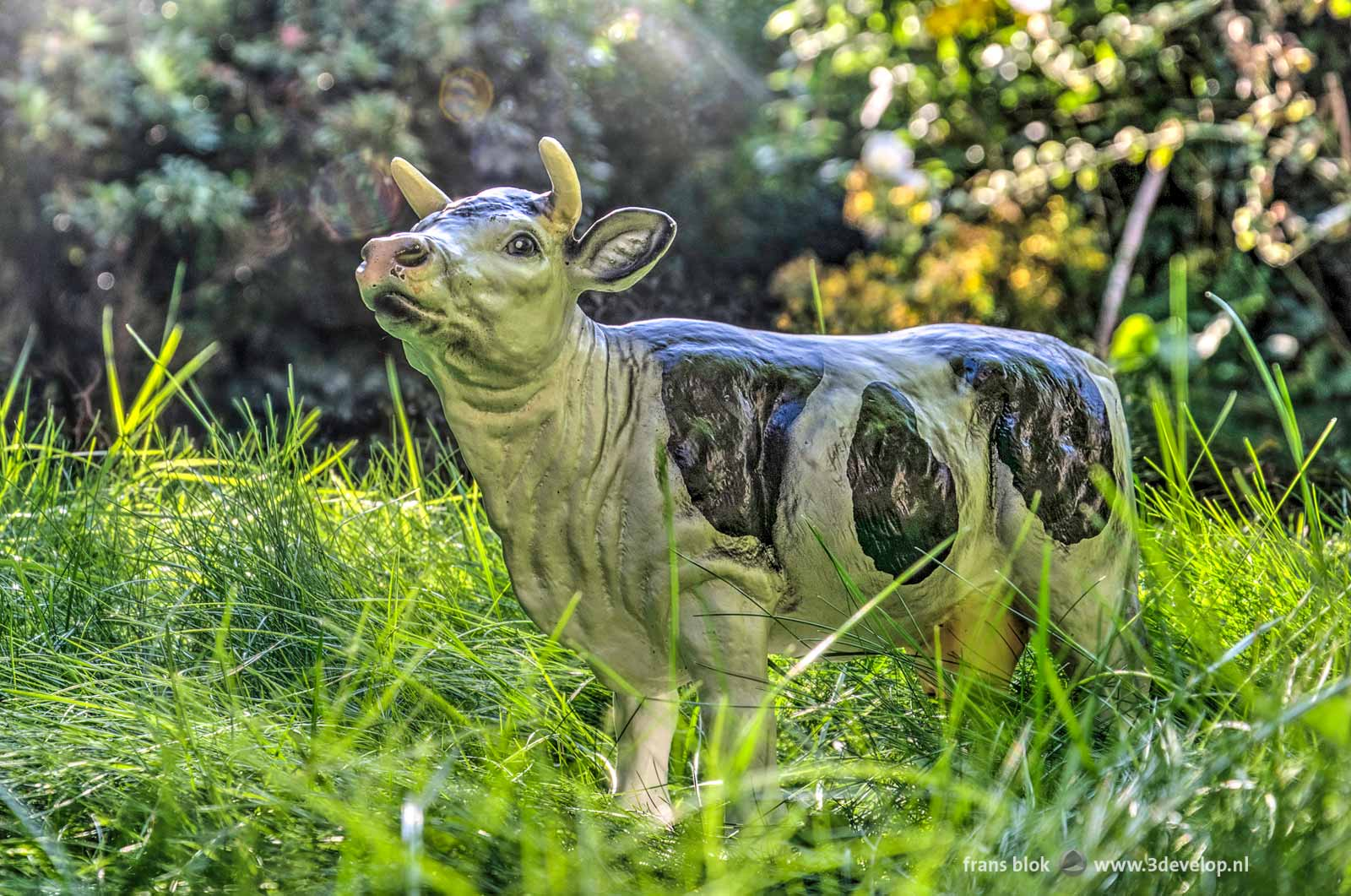 Stone sculpture of a cow in a city garden with tall grass