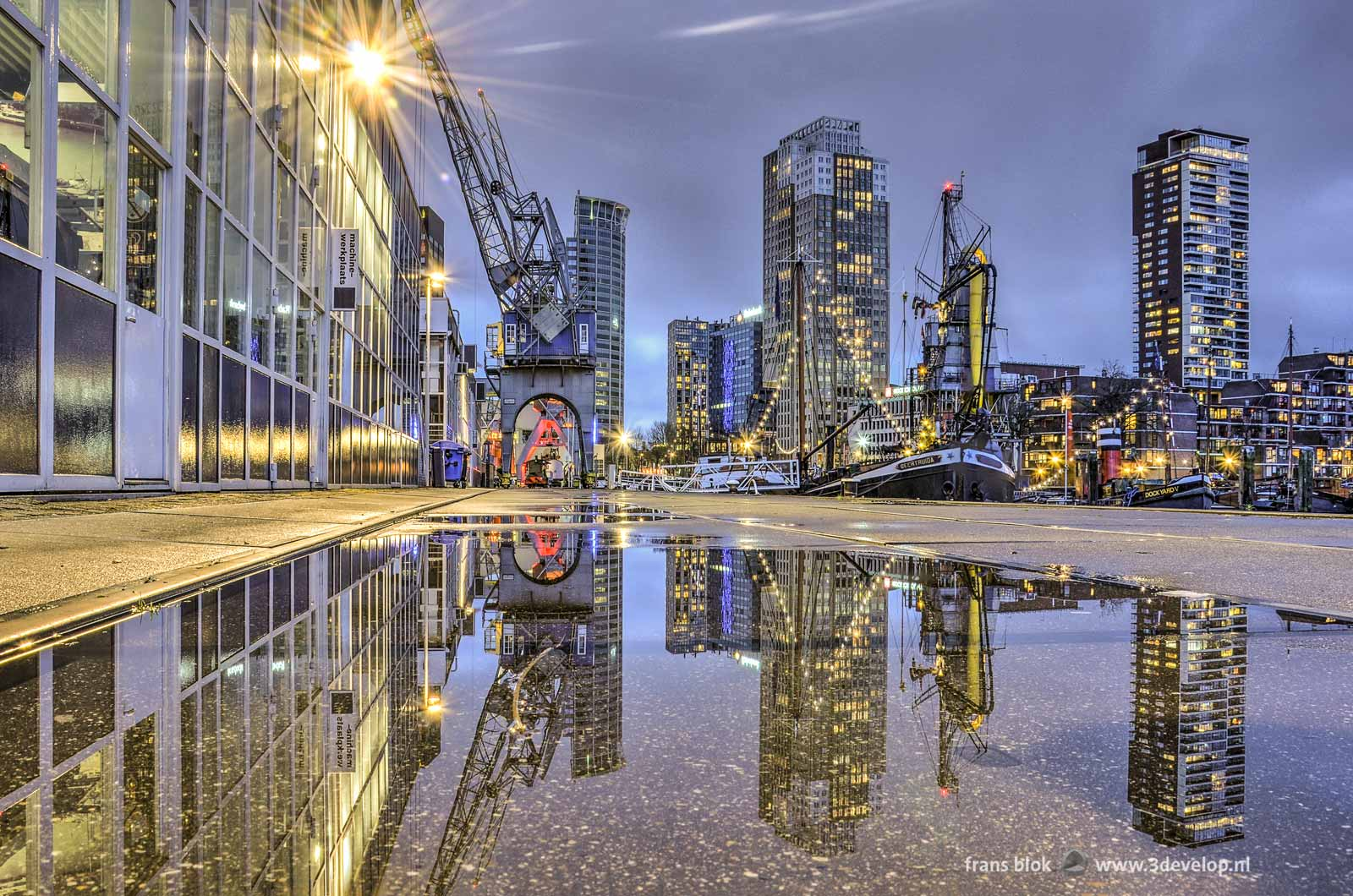 Puddlegram: reflection of cranes, boats, grain elevator as well as office and residential towers in a puddle on the quay at the Maritime Outdoor Museum on Leuvehaven in Rotterdam