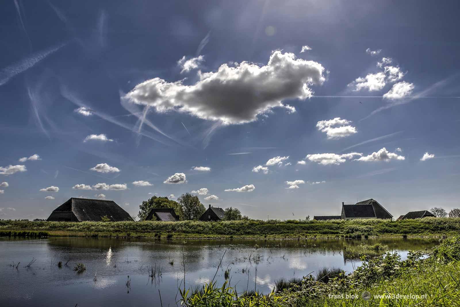 Blauwe lucht met kleine wolkjes en vliegtuigstrepen boven boerderijen op het Zuid-Hollandse natuureiland Tiengemeten
