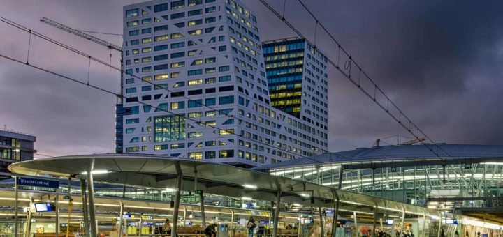 Photo made from one of the platforms on Utrecht Central railway station during the blue hour with the platform canopies, the station hall and the City Office