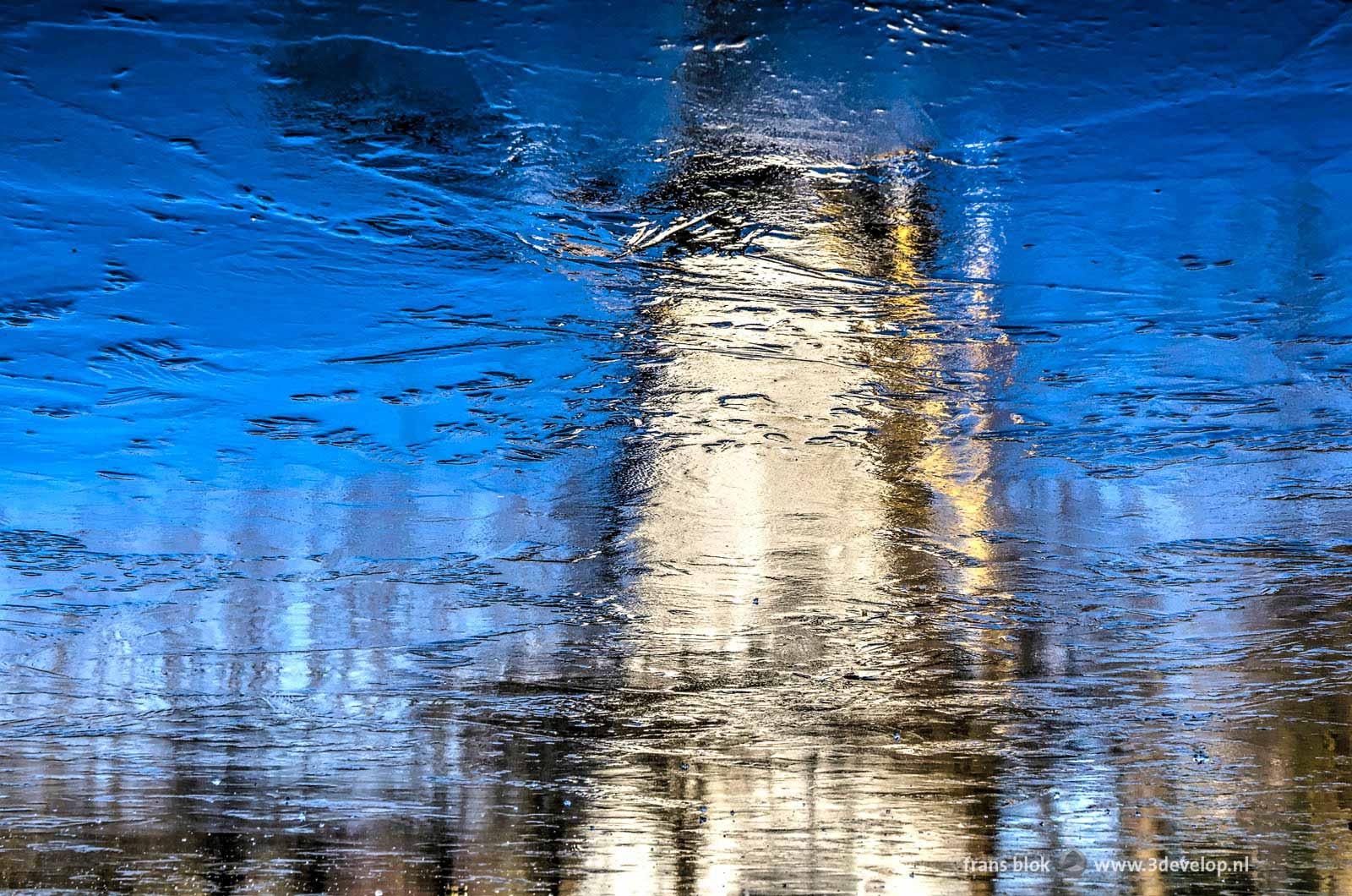 Spiegeling van de molen aan de Kromme Zandweg in Rotterdam-Charlois op het ijs van de vijver.