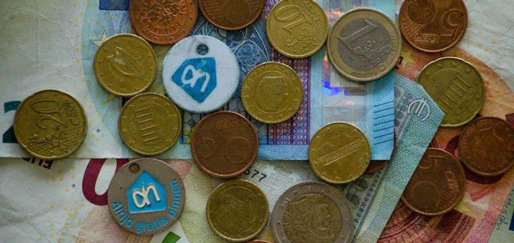 Flatlay van een aantal eurobiljetten en euromunten en een tweetal munten voor de winkelwagentjes van Albert Heijn