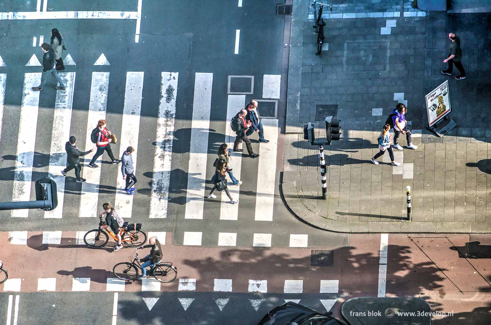 Pedestrians and bicyclists on a street crossing in Rotterdam, seen from above