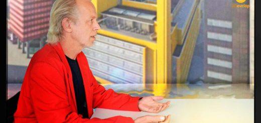 De auteur in een fictieve aflevering van zomergasten, met op de achtergrond een still uit de film over de Bijenkorf van Dudok, spiegelend in het water rond de caravan