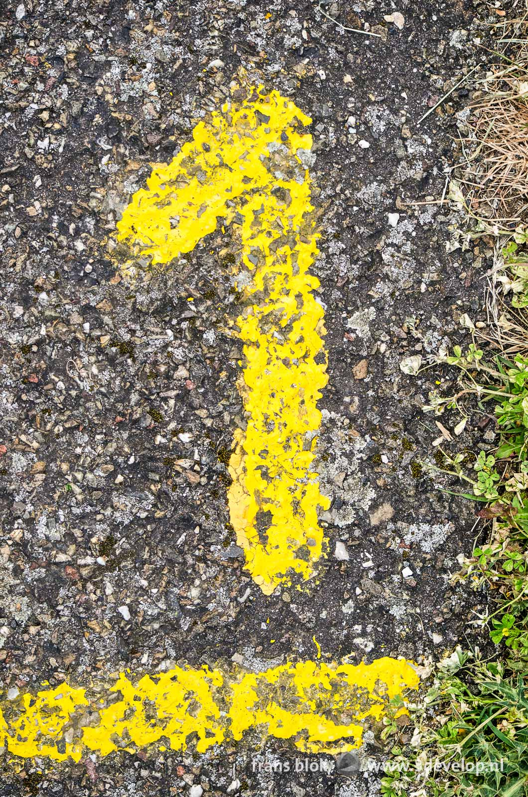 The number 1, painted on asphalt with yellow paint