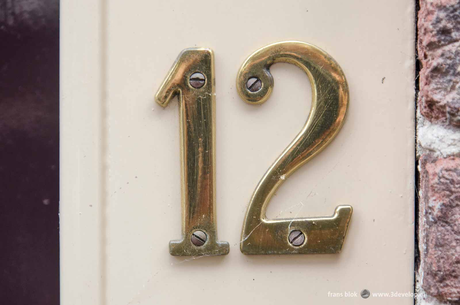 The number 12 as gold leaf house number on a white lacquered wooden background with some remnants of cobwebs on it.