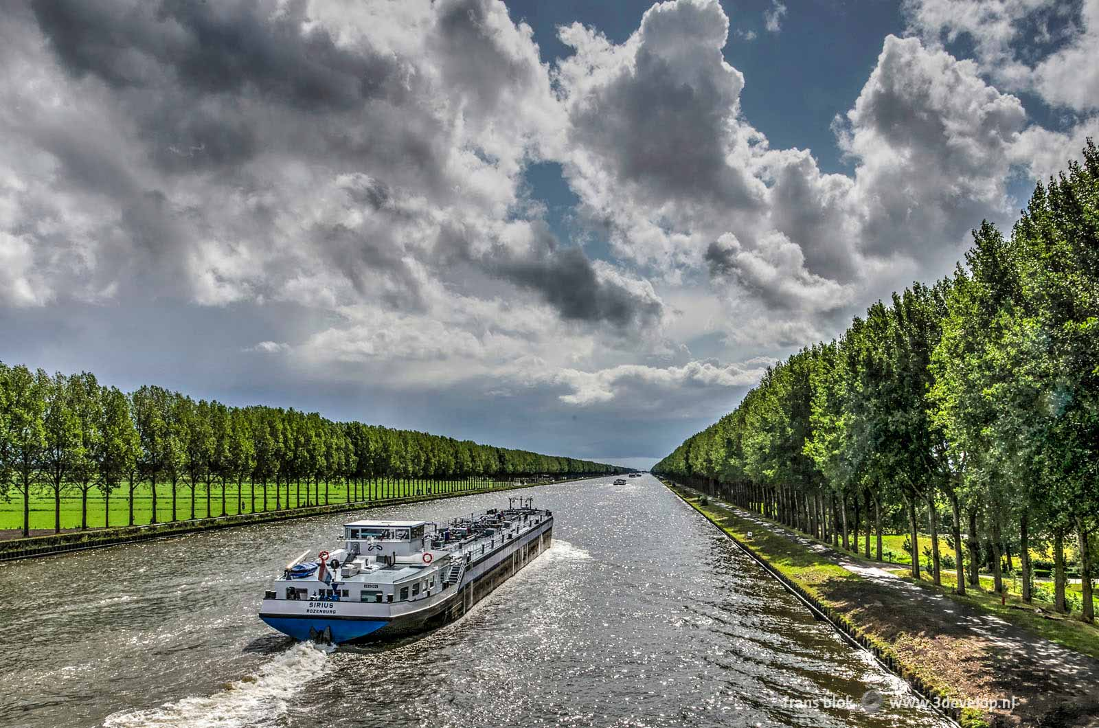 Perspective image of an inland barge on the Amsterdam-Rhine Canal with rows of trees on both sides under a dramatic sky