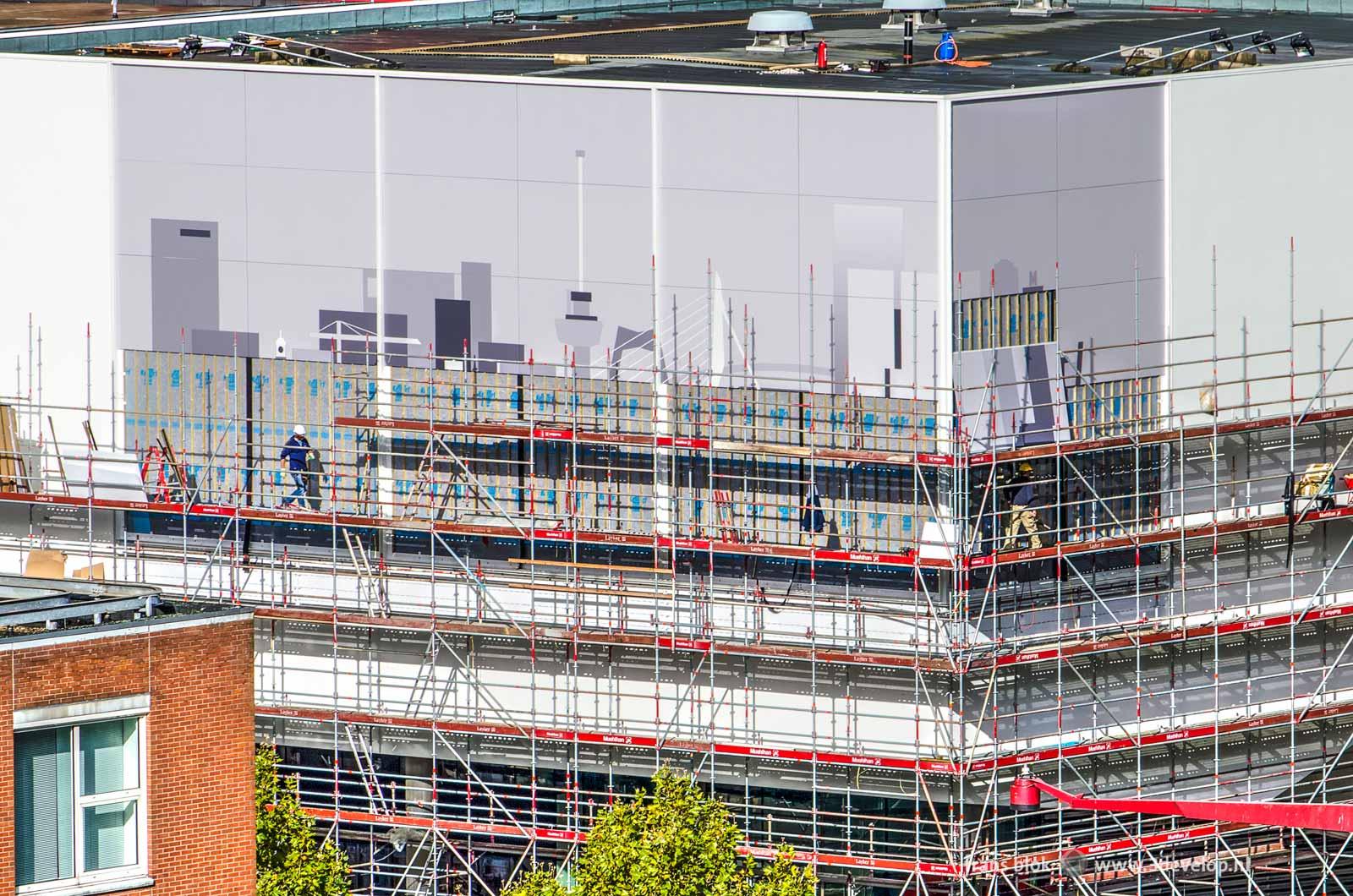 Werk in uitvoering aan de gevel van de Pathé-bioscoop op het Schouwburgplein in Rotterdam, waar de skyline van de stad langzaam te voorschijn komt achter het steigerwerk