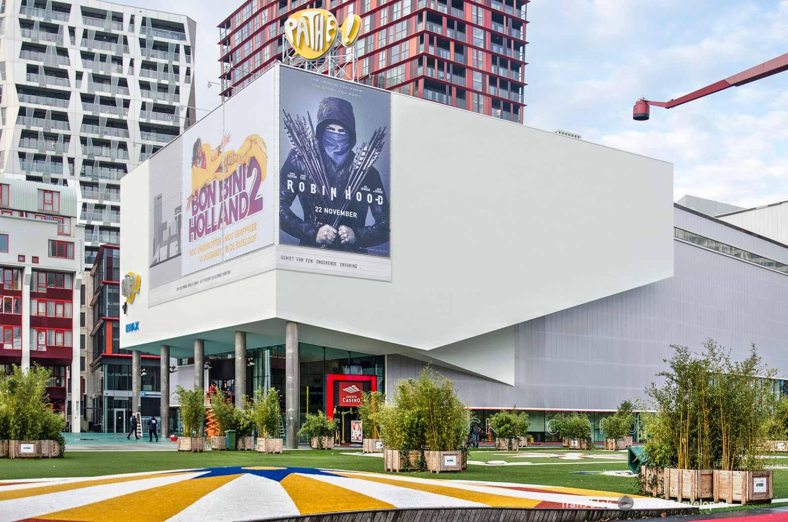 Foto van het Schouwburgplein in Rotterdam, kort na de voltooiing van de renovatie van de Pathé-bioscoop, met filmposters van Robin Hood en Bonbini Holland over het beeld van de skyline