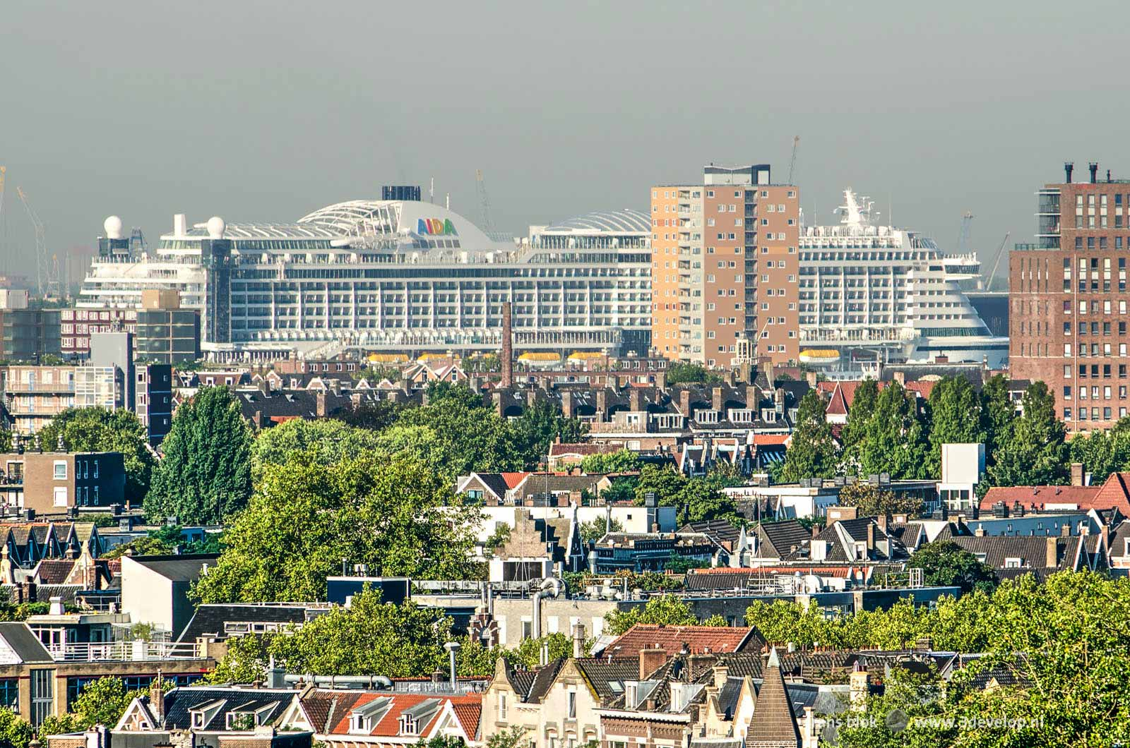 Giant cruiseship Aida on the Nieuwe Maas river in Rotterdam, with old and new neighbourhoods in the foreground