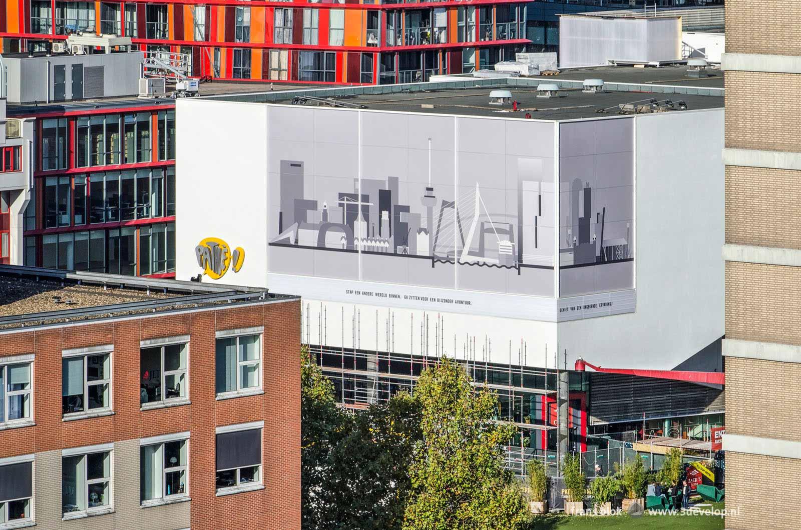 Beeld vanaf een van de Lijnbaanflats op de pas gerenoveerde bioscoop van Pathé op het Schouwburgplein met op de gevel de skyline van Rotterdam