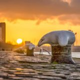 Close-up of a bollard between the cobble stones on the quay of Wilhelmina Pier in Rotterdam, The Netherlands with in the background a fiery sunset over Charlois neighbourhood