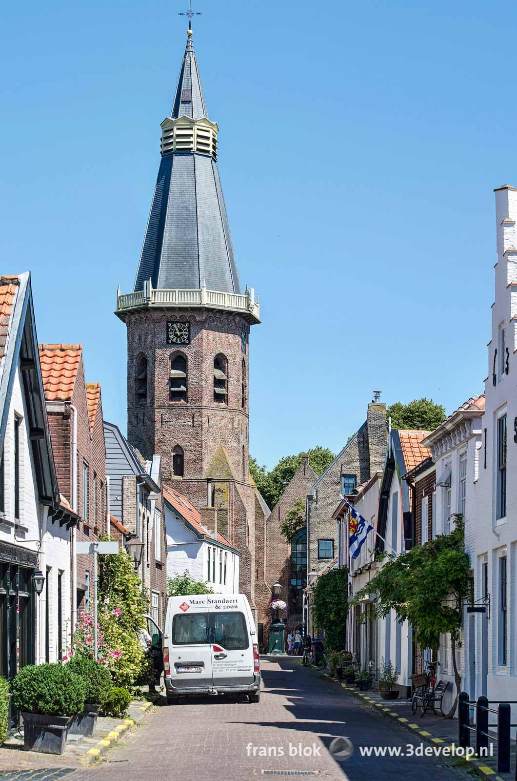 Straatje leidend naar de kerk in Groede in Zeeuws Vlaanderen met een witte bestelbus ontsierend midden in het beeld