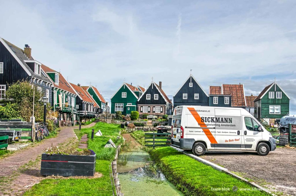 Unsightly white van, parked on the green area behind a row of traditional wooden houses on the island of Marken, The Netherlands