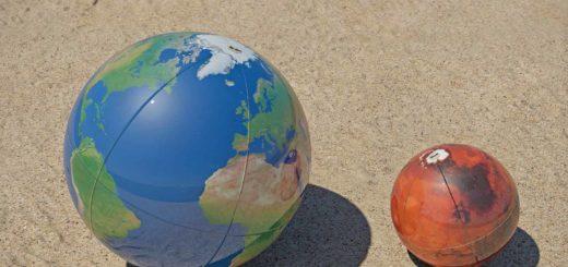 De planeten Aarde en Mars als twee strandballen in het zand, op de juiste schaalverhouding ten opzichte van elkaar.