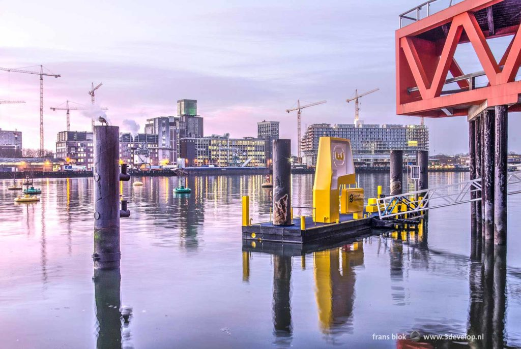 Rijnhaven harbour in Rotterdam with a yellow jetty and a red truss of the New Luxor theatre during sunrise, with the grainsilo and the Fenixlofts at Katendrecht in the background