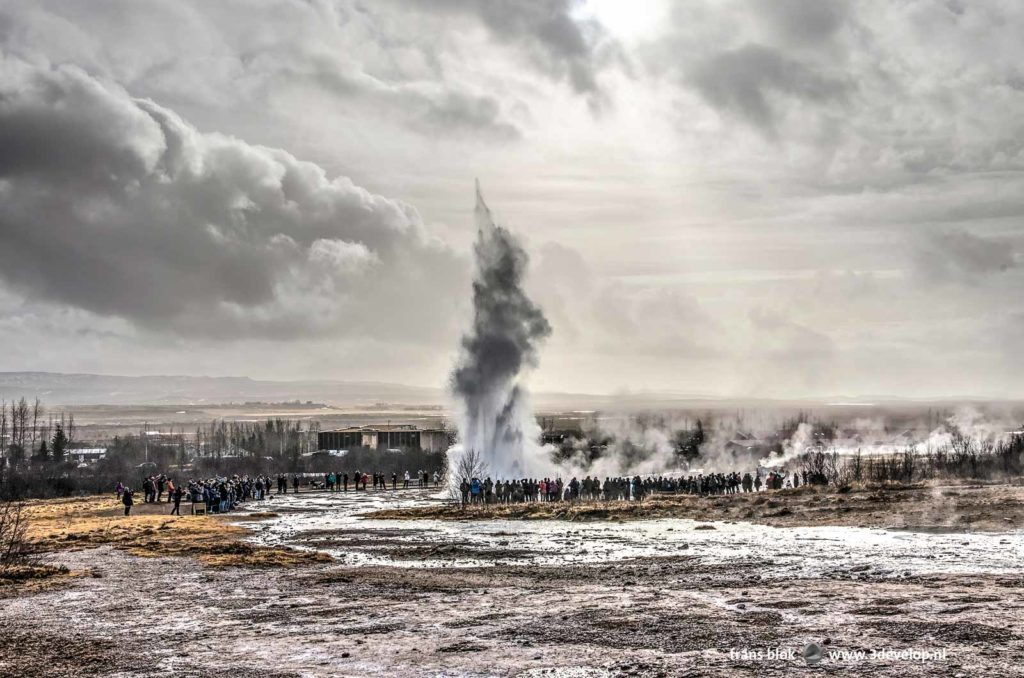 Strokkur geyser in Iceland, not far from the historic Geysir geyser, during an eruption, watched by hundreds of tourists