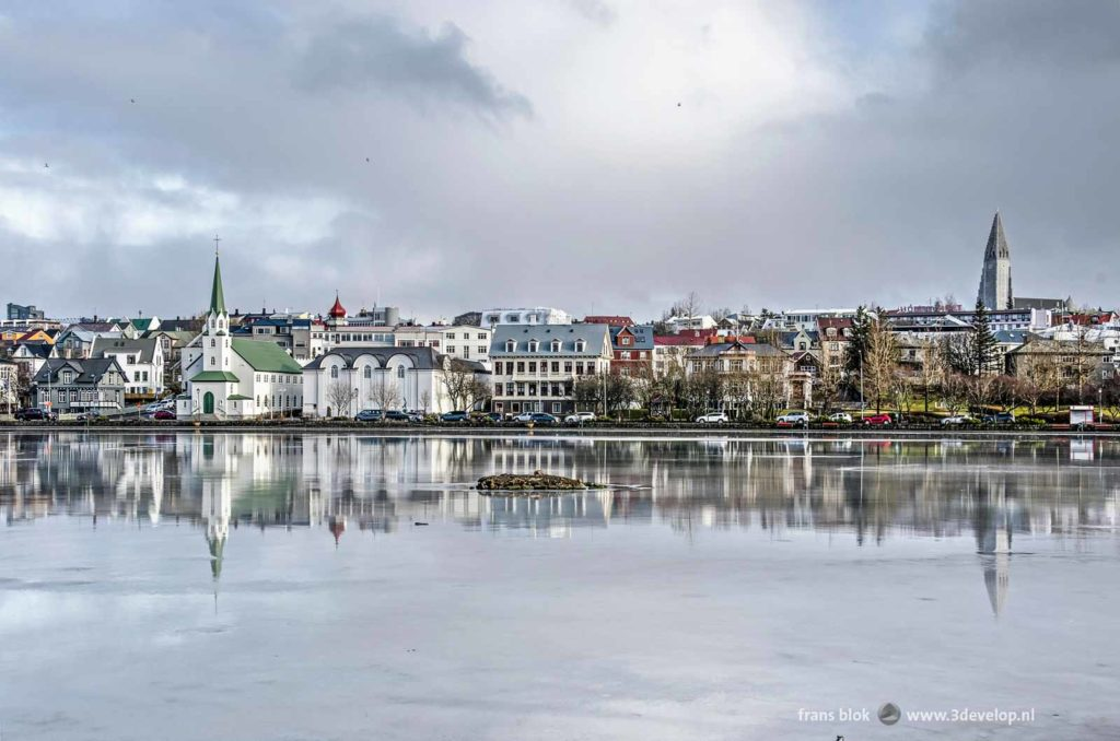 Colorful houses and two churches in the center of Reykjavik, Iceland, reflecting in the ice on lake Tjörnin
