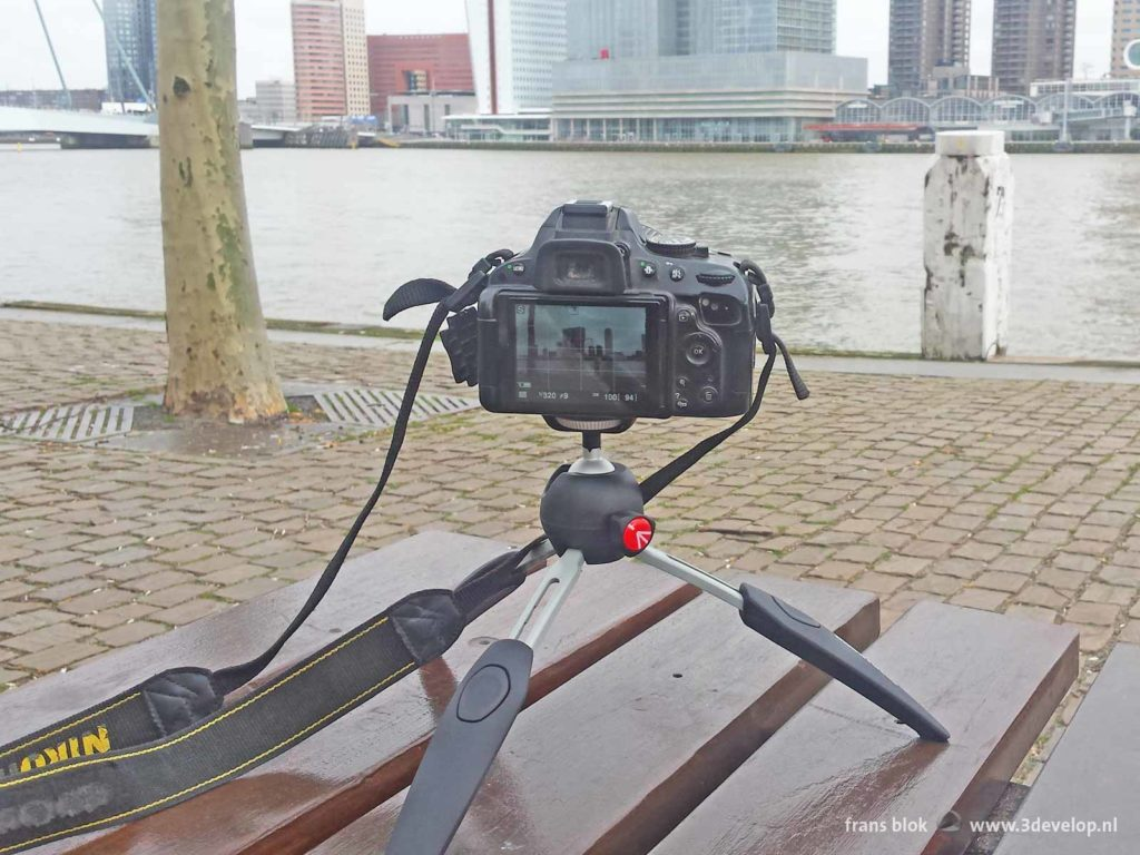 A Manfrotto Pixi Evo mini tripod with a Nikon D5100 camera mounted on it, on the Willemskade overlooking the Wilhelminapier in Rotterdam